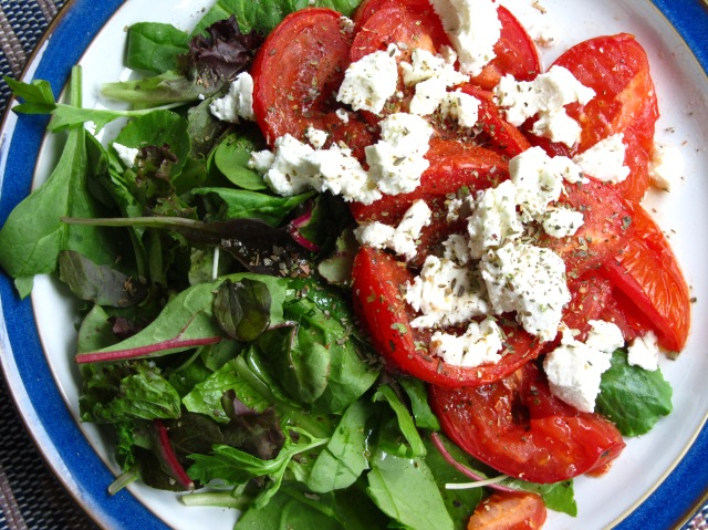 roasted tomatoes on greens with goat cheese